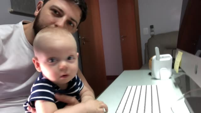 dad and son on a video call at home office - son stock videos & royalty-free footage