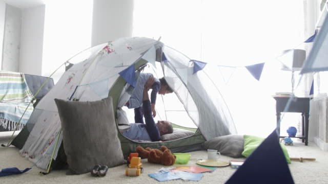 dad and son play together in fort indoors. - tent stock videos and b-roll footage