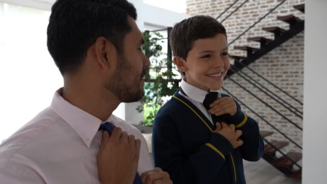 dad and son talking while dad teaches him how to do his necktie both smiling - necktie stock videos & royalty-free footage