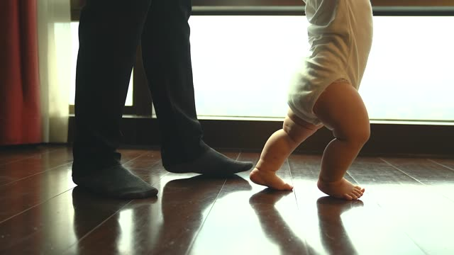 dad and son walking, father helps a child to make baby steps evening in their home. father playing with his baby after work. - steps stock videos & royalty-free footage