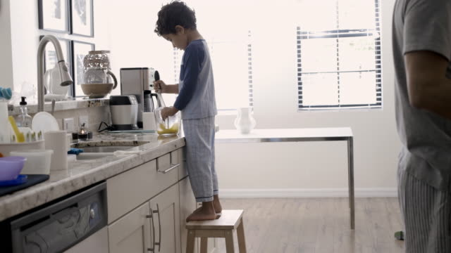 WS Dad and young son making breakfast in kitchen