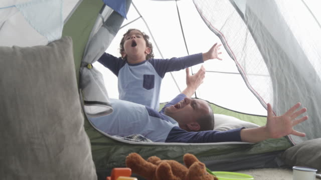 Dad and young son stretching arms and waking up in play fort.