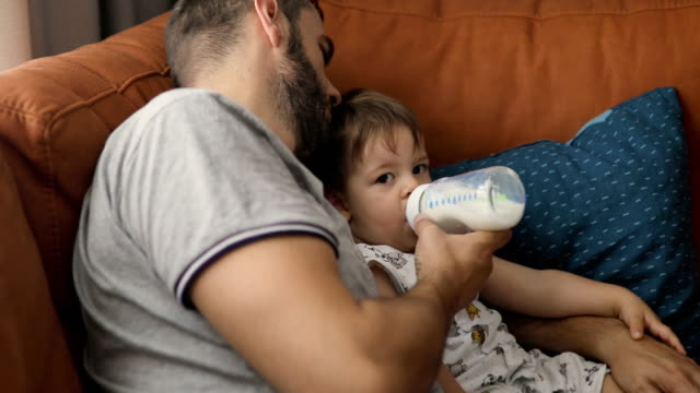 dad bottle feeding toddler son - toddler stock videos & royalty-free footage