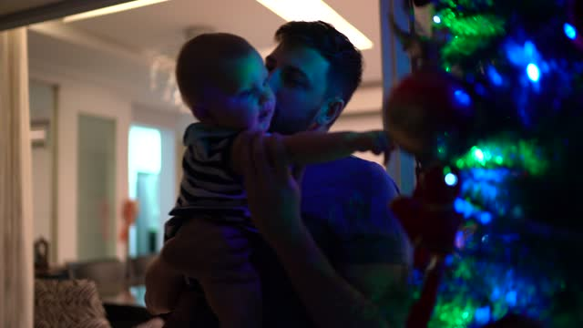 vídeos y material grabado en eventos de stock de papá llevando al niño y mostrando el árbol de navidad iluminado - carrying