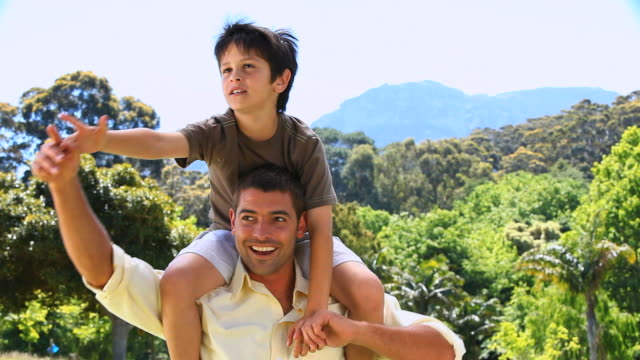 MS Dad carrying son and enjoying the time together in Park / Cape Town, Western Cape, South Africa