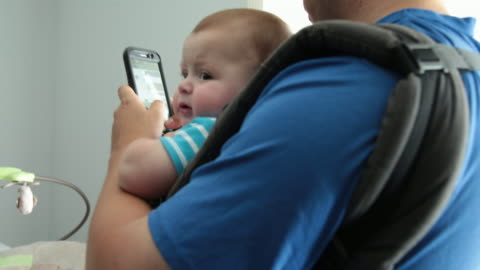 dad checking messages on phone holding baby in baby carrier - multitasking stock videos & royalty-free footage