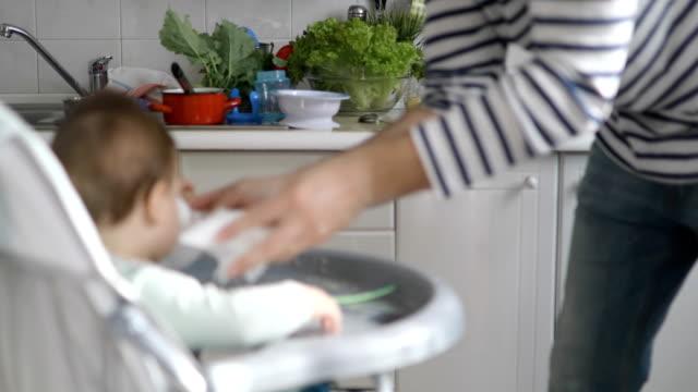 papa, reinigung, baby und verwirrung, die sie bei der fütterung gemacht - chaos stock-videos und b-roll-filmmaterial