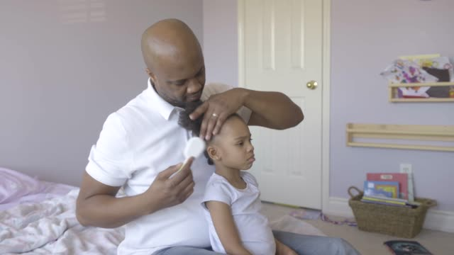 Dad combing young daughter's hair.
