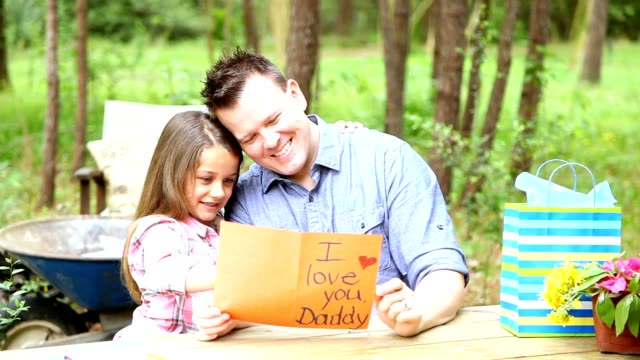 vídeos de stock e filmes b-roll de dad, daughter outdoors with father's day or birthday gifts. - giving