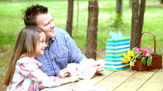 Dad, daughter outdoors with Father's Day or birthday gifts.