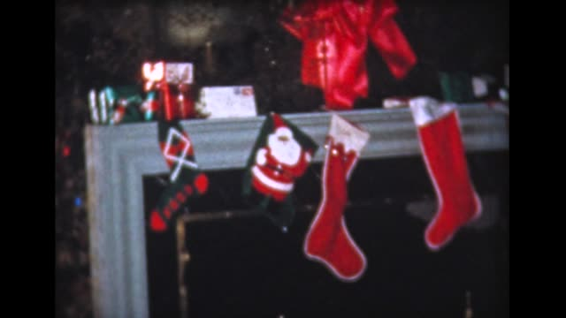 1959 dad decorates xmas tree, lots of presents - 1950 1959 stock-videos und b-roll-filmmaterial