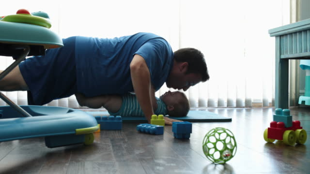 dad exercising at home with baby son, baby laying on floor laughing - push ups stock videos & royalty-free footage