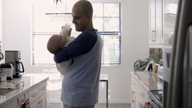ws dad feeding baby in kitchen - differential focus stock-videos und b-roll-filmmaterial