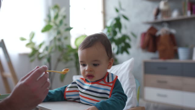 dad feeding toddler boy for breakfast - genderblend stock videos & royalty-free footage