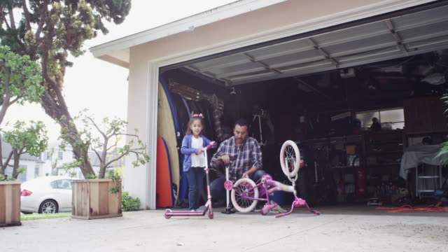 dad fixing bike and daughter playing going around with a scooter - garage stock-videos und b-roll-filmmaterial