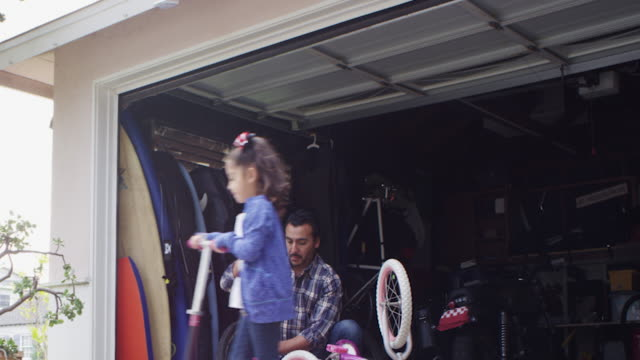 Dad fixing bike and daughter playing going around with a scooter