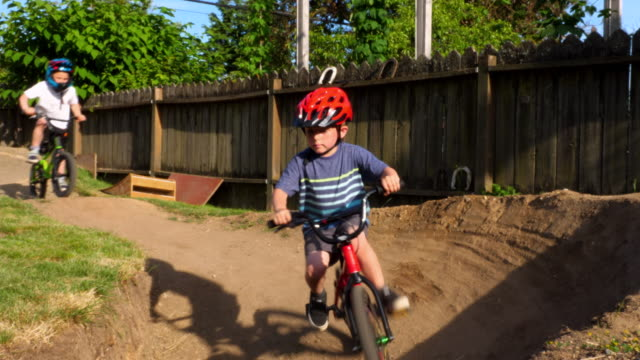 vídeos y material grabado en eventos de stock de ms dad following four young friends riding bmx bikes on backyard dirt track on summer afternoon - familia con cuatro hijos