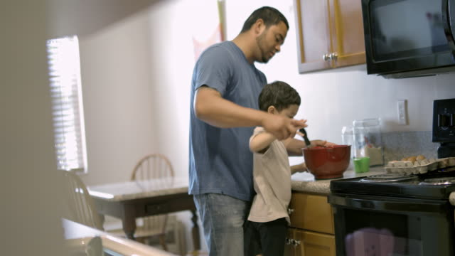 vídeos de stock e filmes b-roll de dad gets young son to help him mixing in bowl - genderblend
