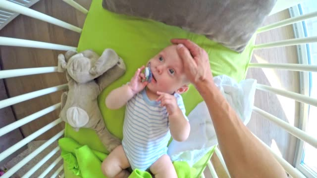 POV Dad gives his baby lying in the crib a pacifier