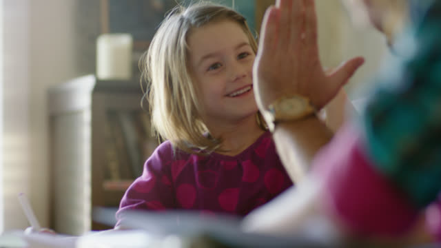 ms. dad gives young daughter high five as she colors with magic marker. - homework stock videos & royalty-free footage