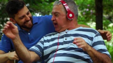 vídeos y material grabado en eventos de stock de papá / abuelo e hijo bailando y riendo en el parque - nieto