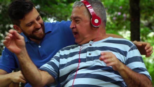 dad / grandfather and son dancing and laughing in the park - senior men stock videos & royalty-free footage