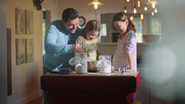 ws. dad has fun stirring pancake batter with daughters while fixing breakfast in pajamas. - morning breakfast stock videos & royalty-free footage