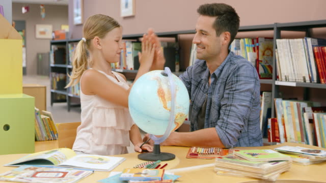 ds padre aiutando la figlia con il mondo in biblioteca imparare - table top shot video stock e b–roll