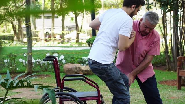 stockvideo's en b-roll-footage met papa die zijn zoon helpt die in zijn rolstoel in het park zit - zoon