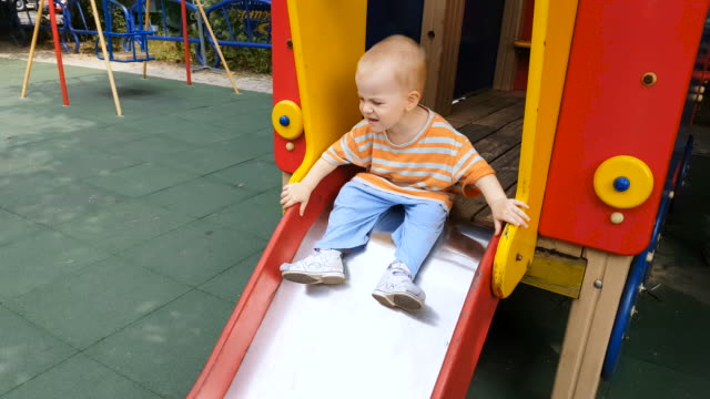 dad helping son to come down from the slide - genderblend video stock e b–roll