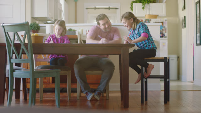 WS. Dad helps daughters with homework at dining room table after school.