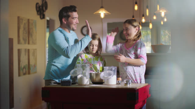 WS. Dad helps kids fix breakfast in the morning and gives daughter high five.