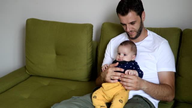 vidéos et rushes de papa holding et de parler à son petit garçon - genderblend