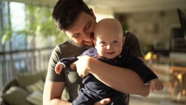 pappa håller sin son hemma - män i 30 årsåldern bildbanksvideor och videomaterial från bakom kulisserna