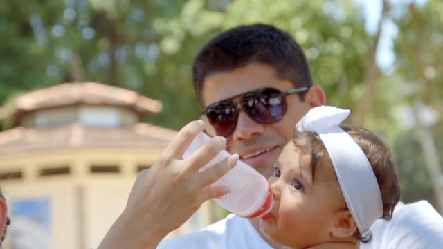 Dad holds baby girl while mother gives her water from bottle in public park
