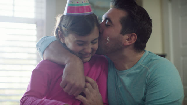 ms. dad hugs and kisses daughter as she rubs cake frosting on his cheek at birthday party. - party hat video stock e b–roll