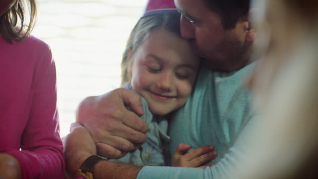 CU. Dad hugs and kisses daughter's forehead as big sister licks cake frosting at family birthday party.