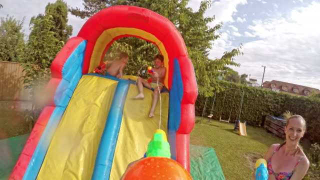 pov dad in a water gun fight with his wife and kids - squirt gun stock videos and b-roll footage