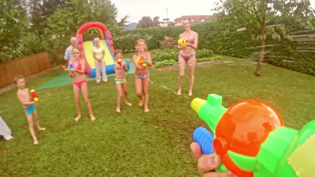 POV Dad in water gun fight with kids at a children's party
