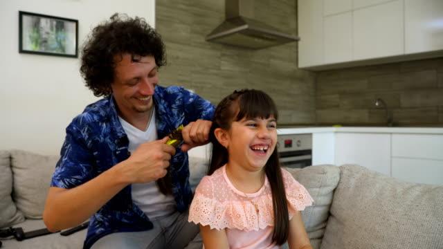 stockvideo's en b-roll-footage met de papa kamt zijn dochterhaar - kammen