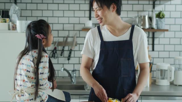 お父さんは昼食を作り、キッチンで小さな女の子とおしゃべり - daughter点の映像素材/bロール