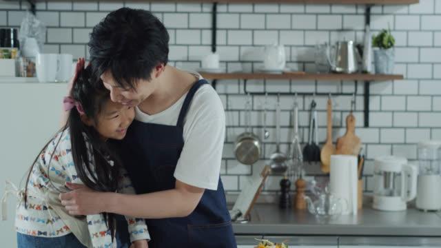 お父さんは昼食を作り、小さな女の子を抱きしめる - daughter点の映像素材/bロール