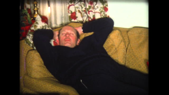 vídeos de stock, filmes e b-roll de 1976 dad naps on couch near christmas tree - home movie