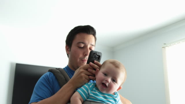 dad pacing around room messaging on phone with baby in baby carrier - baby carrier stock videos & royalty-free footage
