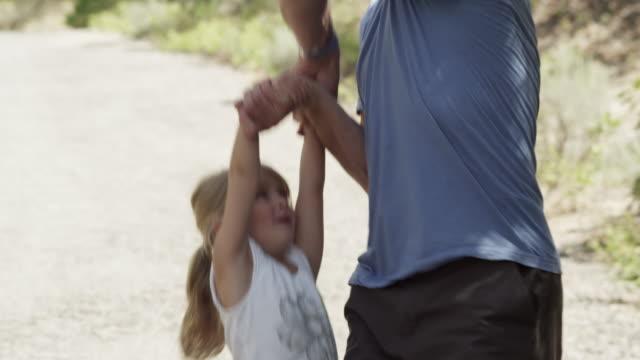 vídeos de stock e filmes b-roll de dad picks up daughter and swings her over his back. - carregar uma pessoa nos ombros