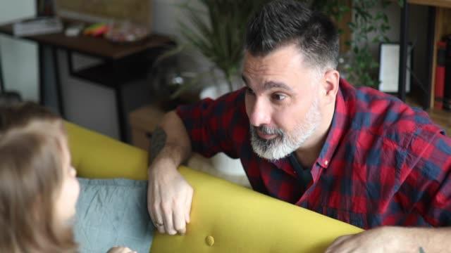 vídeos de stock e filmes b-roll de dad playing peek a boo with his little daughter - masculinidade moderna