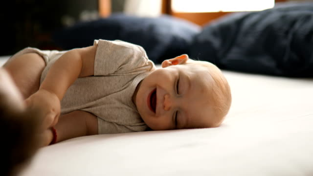 vídeos de stock, filmes e b-roll de pai joga com o bebê na cama - pijama