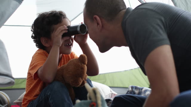 dad playing with son in tent indoors, looking through home made binoculars. - pillow stock videos & royalty-free footage