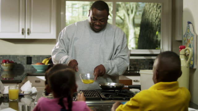 MS Dad pouring scrambled eggs into skillet while Daughter and son watching / Dallas, Texas, USA