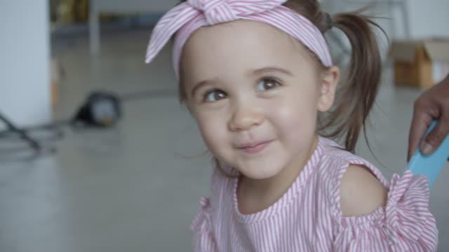 stockvideo's en b-roll-footage met papa die zijn dochter in de wagen bij huis duwt, langzame motie - haaraccessoires